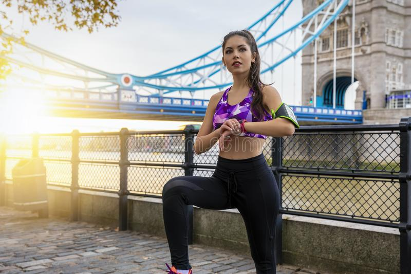 Sports woman takes a break after an early sunrise workout session. Attractive urban sports woman takes a break and checks her progress after an early sunrise royalty free stock images