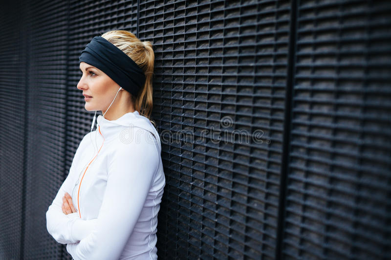 Sports woman taking a break from outdoor training session. Image of attractive and sporty young woman standing against a wall looking away. Taking a break from stock photography