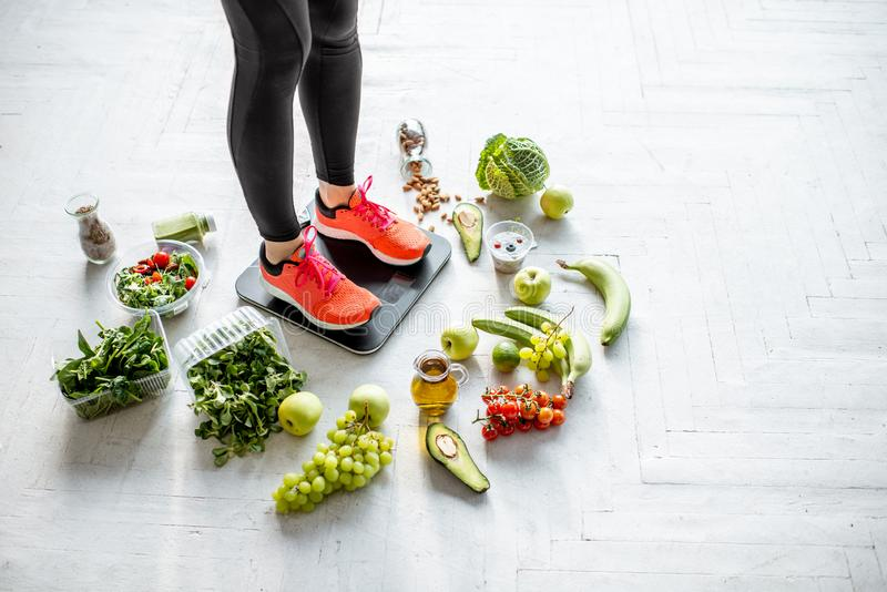 Sports woman weighing with healthy food around. Sports woman weighing on the scales with healthy food around. Weight loss, healthy food and sports lifestyle stock photography