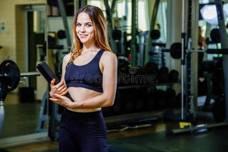 Sports young beautiful woman is an instructor, personal trainer in the gym. Young woman school sport coach. stock photo