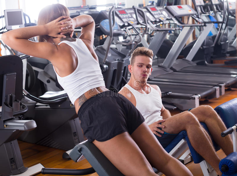 Download Sports Young Man And Woman Training Abdominal Muscles In Gym Stock Photo - Image: 83701549