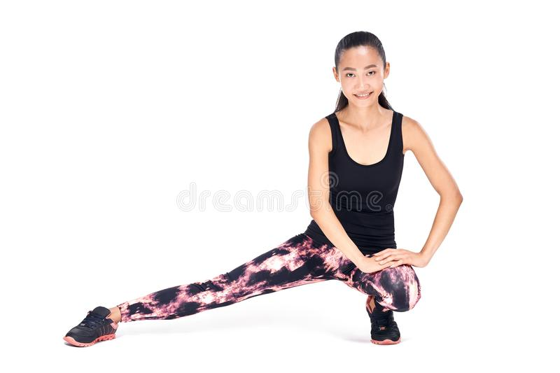 Sports young Oriental woman doing stretching squatting isolated royalty free stock images