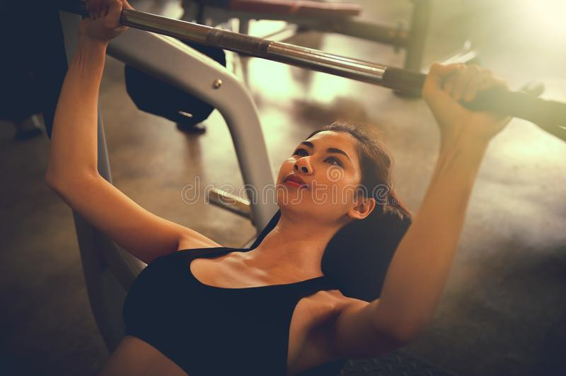 Asia woman with barbell on bench in fitness gym royalty free stock photography