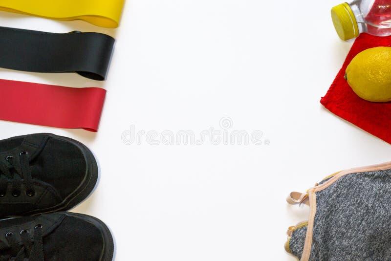 Sportsammansättning av färgrika expanders för elastisk musikband, gymnastikskor, citron, handduk, behå på vit bakgrund med copysp royaltyfria foton