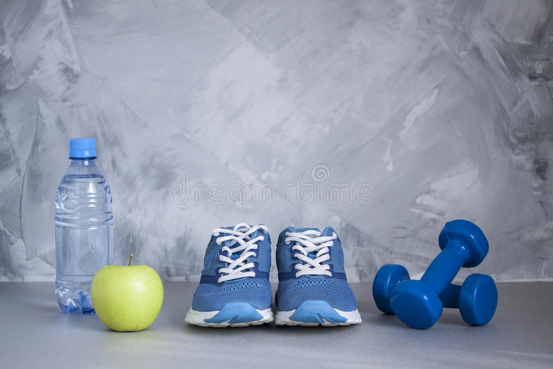 Sportschoenen, domoren, appel, fles water op grijs beton stock fotografie