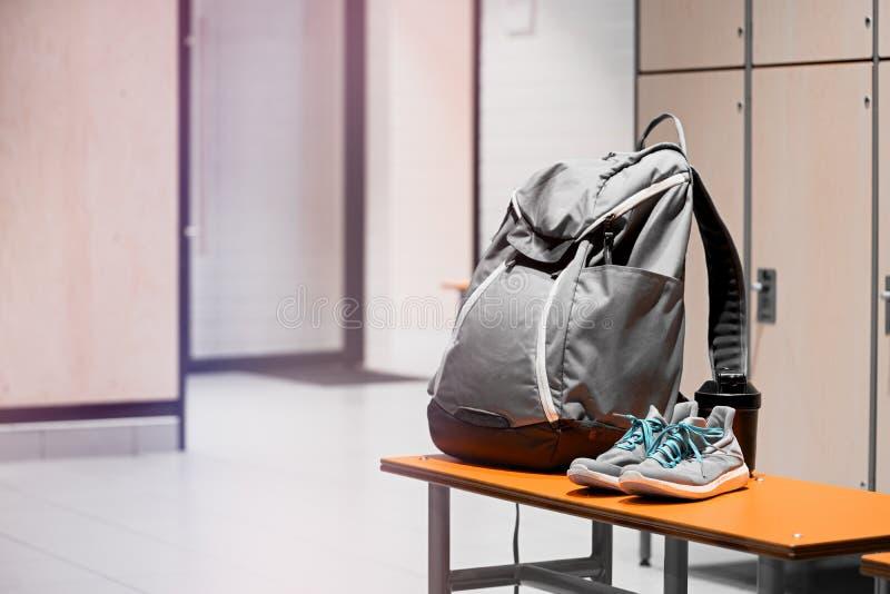 Sportschuhe, Sportrucksack und Sportwasserflasche im Turnhallenumkleideraum stockbilder