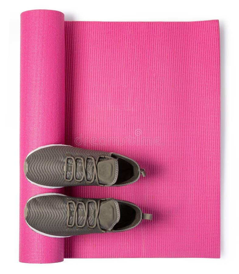 Sportschuhe und Yogamatte lizenzfreie stockfotos