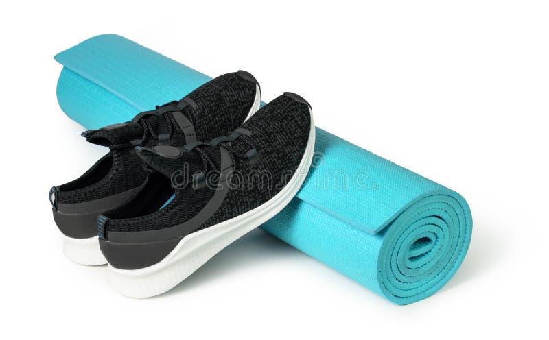 Sportschuhe und Yogamatte lizenzfreie stockfotografie