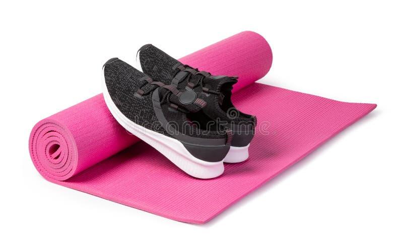 Sportschuhe und Yogamatte stockfoto