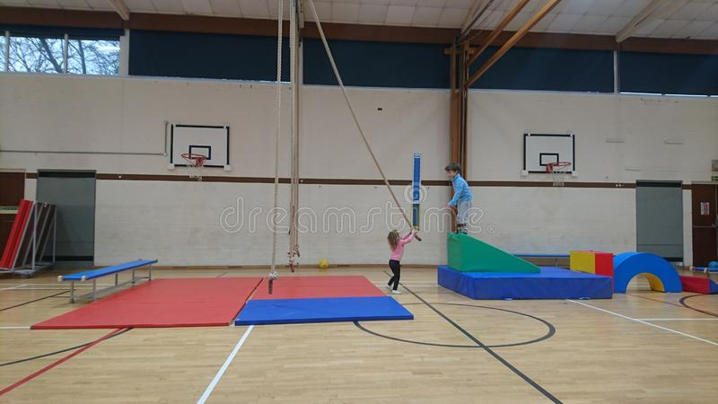 Little girl handing a climbing rope to her brother. Sportshall physical education school fun big huge test endeavour travel explore navigate a route adventure stock photo