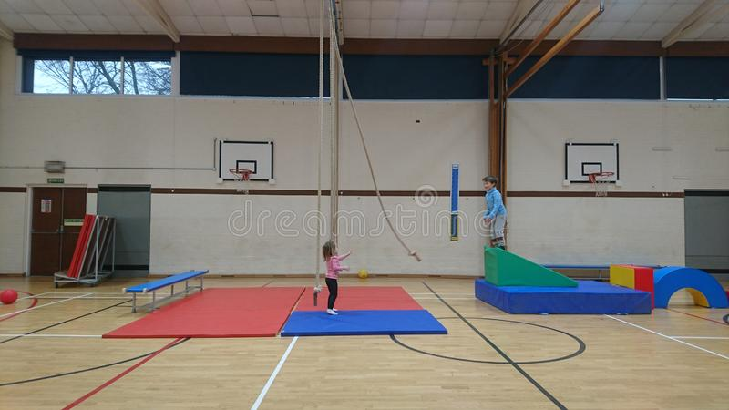 Little girl swinging a climbing rope to her brother. Sportshall physical throwing sending passing delivering waiting anticipating focusing flinging readiness royalty free stock photography