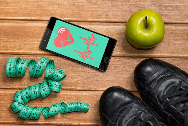 Sportskor, Apple och att mäta bandet och en telefon med det vård- kortet på en träbakgrund Mobil vård- avkännare för app för att  royaltyfri fotografi