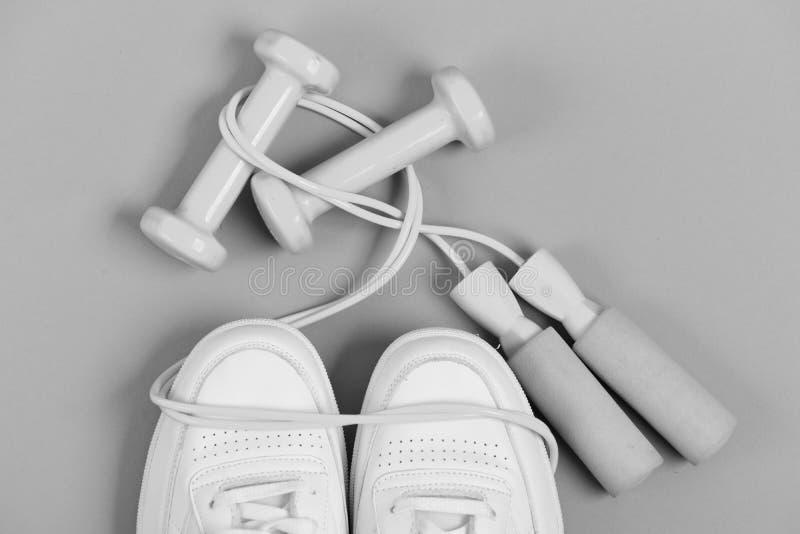 Sportskor och sportive utrustning för sund form Hantlar i cyan blått färgar på vita instruktörer, bästa sikt arkivbild