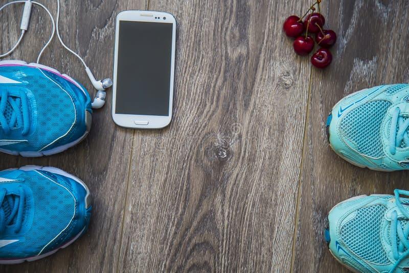 Sportskor, telefon och ilar klockan med uppsättningen för sportaktiviteter på golv royaltyfri foto