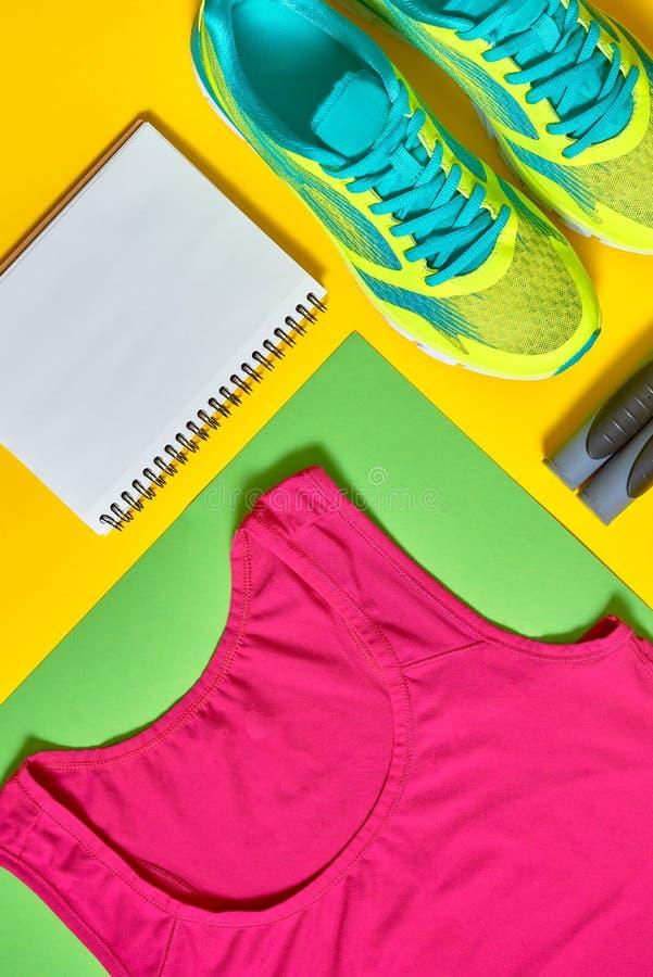 Sportskor, woman& x27; bästa behå för s, vitt tomt anteckningsbok- och överhopprep på färgrik gul och grön backgroundon, kopierin arkivbild