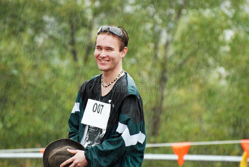 Sportslig konkurrent för stilig ung australisk man som fångas i regn royaltyfria bilder