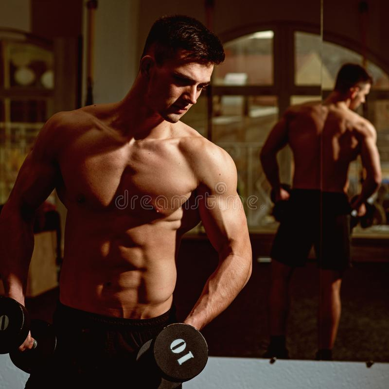 Sportsman, athlete with muscles looks attractive. Man with torso, muscular macho and his reflexion in mirror background. Man with nude torso in gym enjoy his royalty free stock image