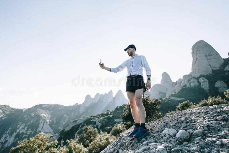 Sportsman or athlete with smartphone on mountain royalty free stock photography
