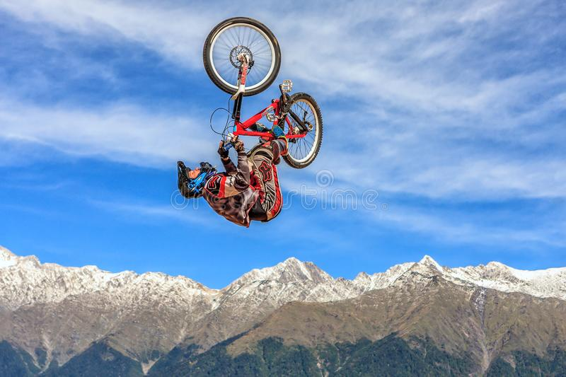 Sportsman biker flies in air with bicycle upside down from jump at bike competition on snowy Caucasus mountain peaks and blue sky royalty free stock images