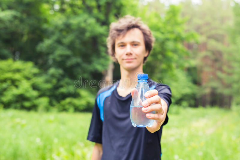 Sportsman with a bottle of water after running outdoors in park. royalty free stock photography