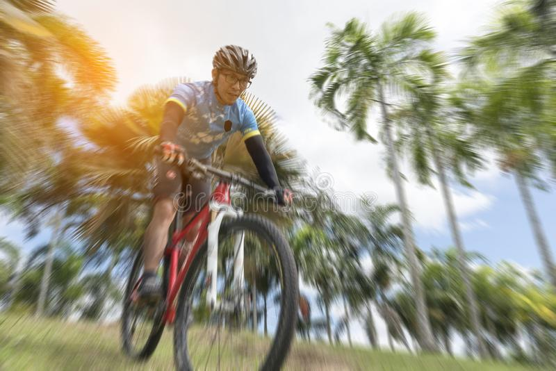Sportsman cycling the bicycle from highland, selective focus, radial blur, Sport concept.  stock images
