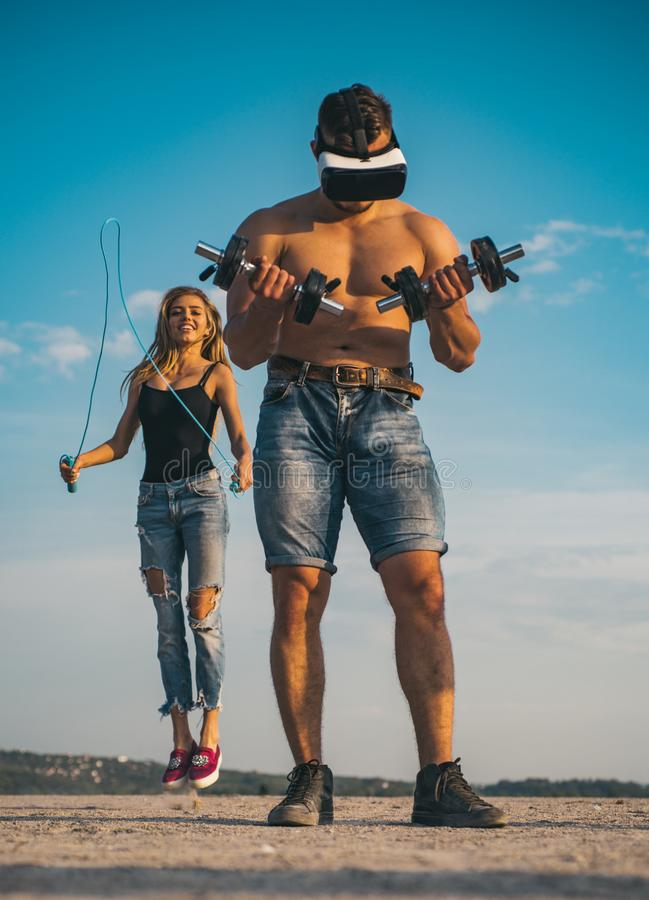 Sportsman with dumbbells. Sportsman wear vr headset for training. Sportsman with fit body and girl skipping on blue sky stock photo