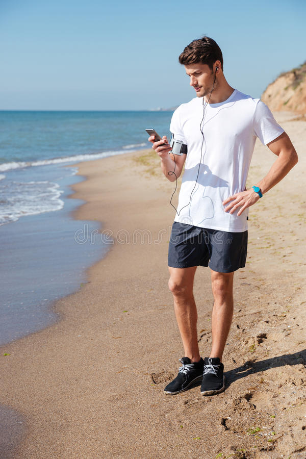 Sportsman with earphones listening to music from mobile phone stock photo
