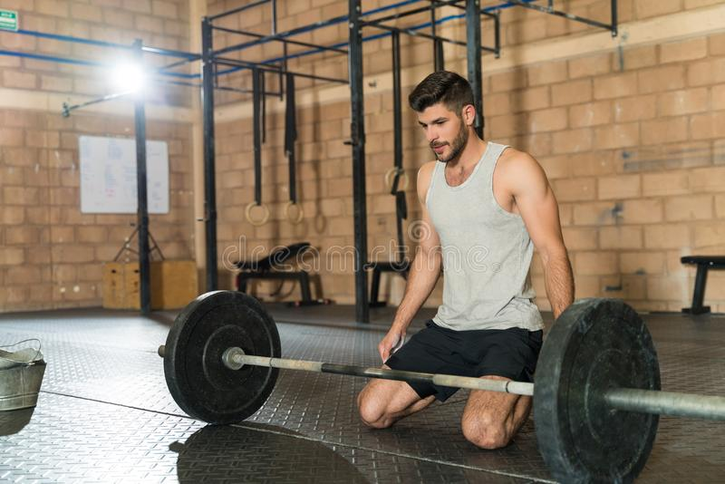 Sportsman At Gym During Cross Training Session. Handsome young male athlete kneeling and preparing himself mentally to lift the barbell at fitness club royalty free stock images