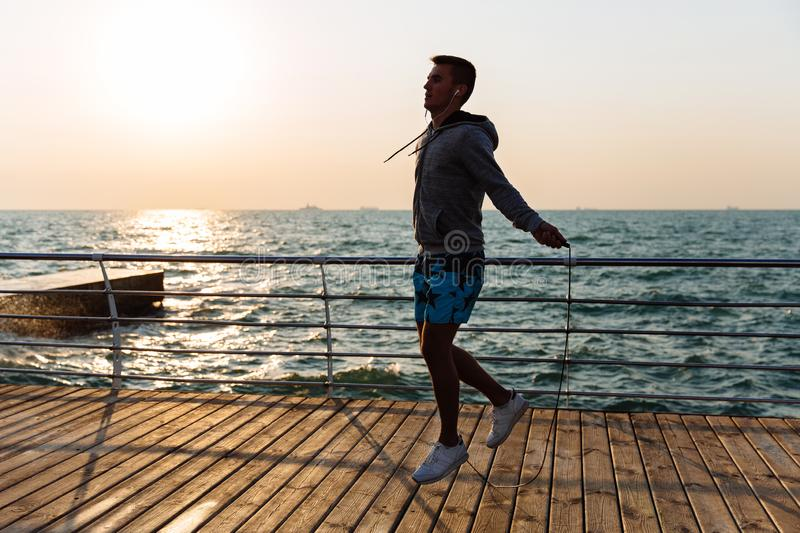 Sportsman in headphones jumping with skipping rope. Young sportsman in sportswear, jumping with skipping rope, listening to music in earphones, on quay, near the stock photo