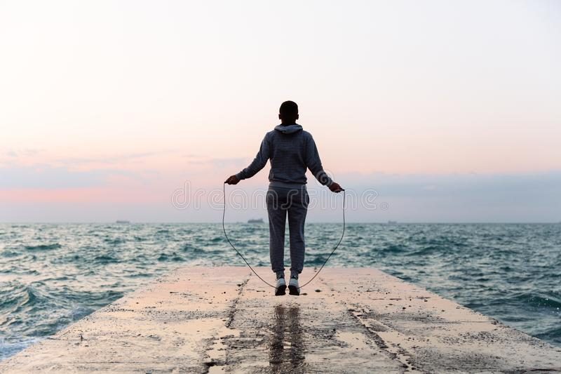 Sportsman jumping with skipping rope, workout on pier. Young sportsman jumping with skipping rope, spending workout on pier, looking at seaside. Back view stock photo