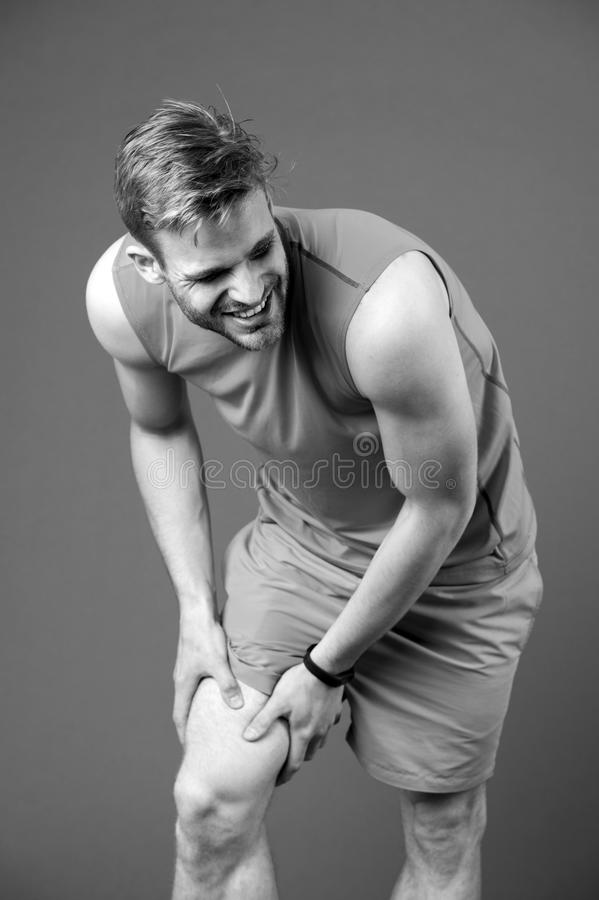 Sportsman with knee pain on violet background. Man in orange vest and blue shorts. Health problem and sore. Medical aid. With treatment and therapy. Sport and stock photo