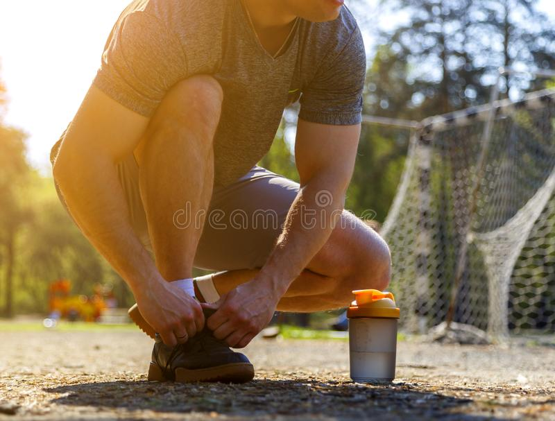 Sportsman laces his sneakers sitting and looking forward. Blurred background with forest, kids playground and football goal royalty free stock photos
