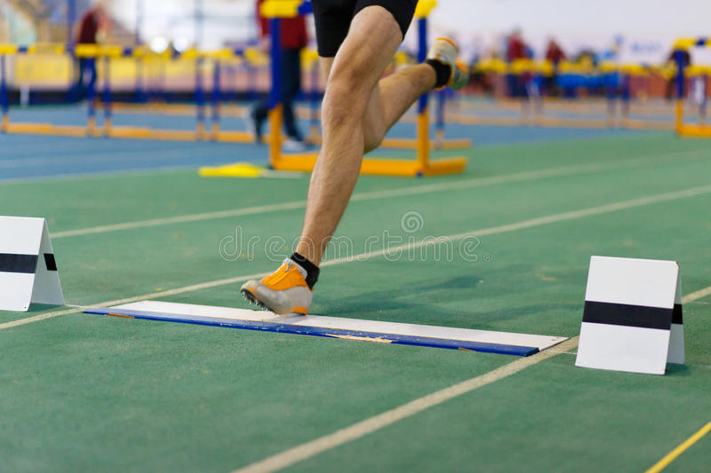 Sportsman landing leg on fault line before jump. Sportsman landing his leg on fault line of board before taking off in long jump or tripple jump competition stock photos