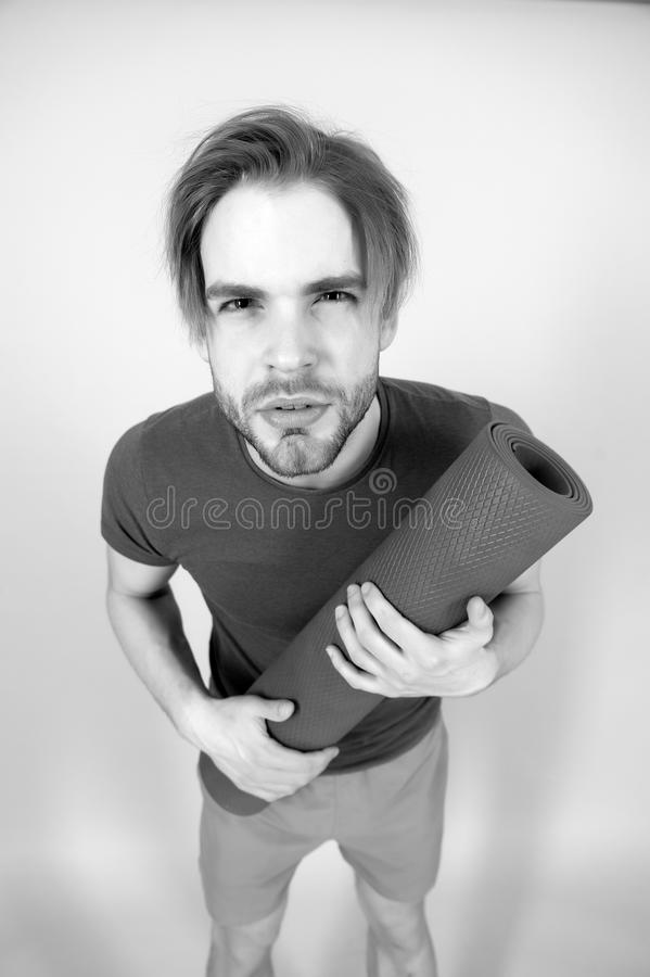 Sportsman look with serious face. Man hold yoga mat. Fashion athlete in blue tshirt and shorts. Gym equipment for. Training and workout. Yoga or pilates and stock photos