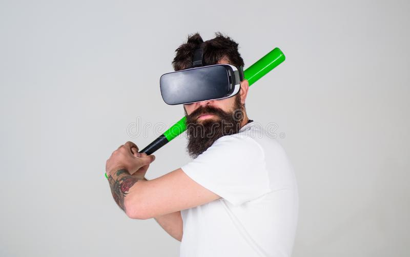 Sportsman mastering batting skills isolated on gray background. Bearded athlete using digital technology in training. Sport concept. Gamer in VR glasses with royalty free stock images