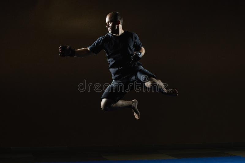 A sportsman in MMA gloves is training a jump for a punch hand stock image