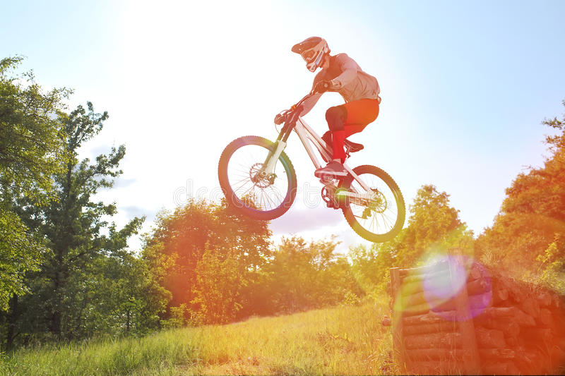 Sportsman on a mountain bike is flying in a jump from a springboard royalty free stock photos