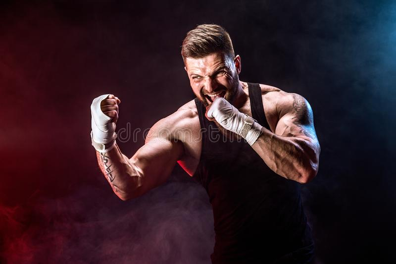 Sportsman muay thai boxer fighting on black background with smoke. stock photography