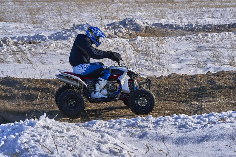 Sportsman racer man fulfills a fast ride on the ATV on the road extreme. The race track is very uneven royalty free stock photo