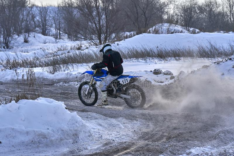 Sportsman racer man fulfills a fast ride on a motorcycle on the road extreme. The race track is very uneven. Photo as the racer p royalty free stock image