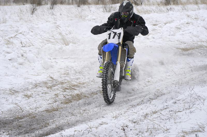 Sportsman racer man fulfills a fast ride on a motorcycle on the road extreme. The race track is very uneven. stock photo