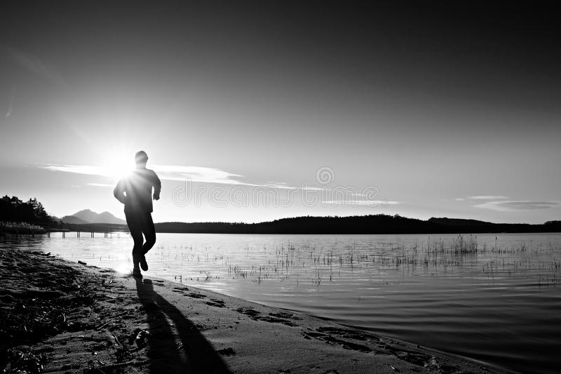 Sportsman running at amazing summer sunset along coastline in sport and healthy life style. Sportsman running at amazing summer sunset along coastline in sport stock images