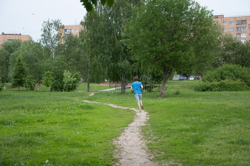 Sportsman is running on the road in the park royalty free stock image