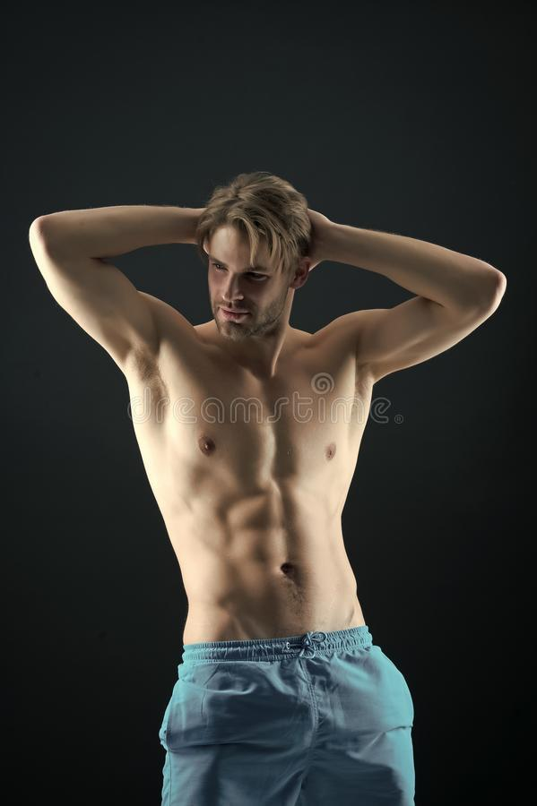 Sportsman with sexy torso and chest. Athlete with fit body in shorts. Man with six pack and ab muscles. Training and royalty free stock image