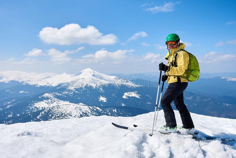 Sportsman skier on skis on background of blue sky and highland landscape. Winter skiing concept. Sportsman skier in helmet and goggles with backpack standing on stock image