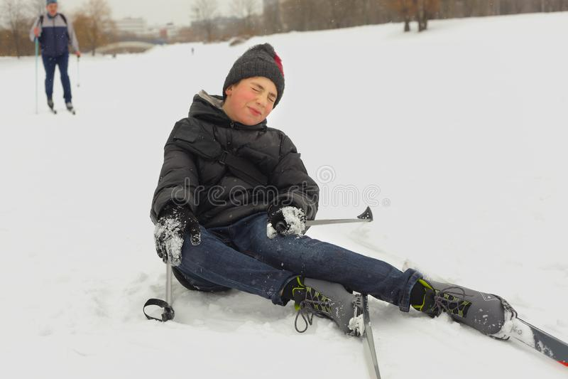 sportsman skier teenager boy fall down on the snow on skiing race competition royalty free stock image