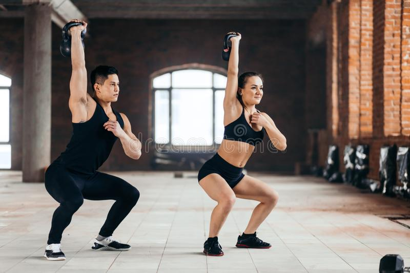Sportsman and sportswoman doing squats with kettlebell in the sport center royalty free stock photography