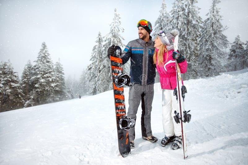 Sportsman and sportswoman on skiing holding ski equipment royalty free stock photo