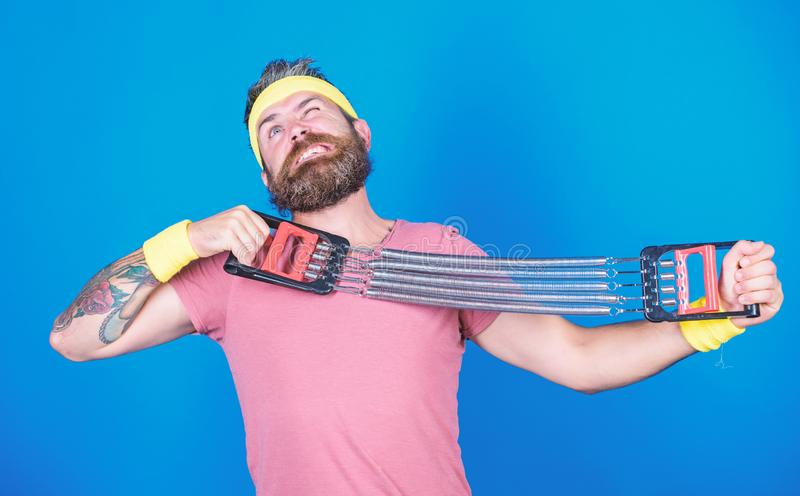 Sportsman stretching expander. Try stretching exercise. Athlete workout with expander. Improve your muscles with sport. Equipment. Man bearded exercising with stock photos