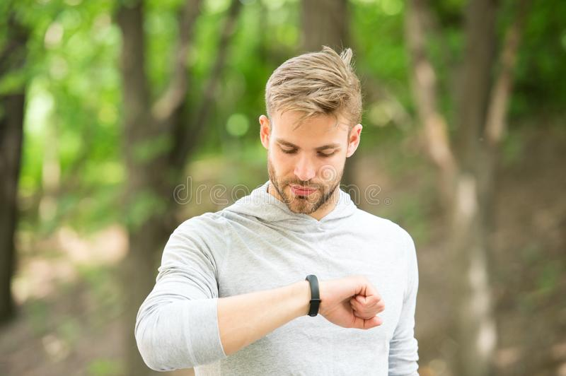 Sportsman training with pedometer gadget. Man athlete on busy face check fitness tracker, nature background. Athlete. With bristle with fitness tracker or stock photo